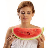 Young woman looking down at slice of watermelon Stock Images