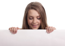 Young woman looking down a white sign Stock Photography