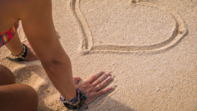 Young Woman Looking at Drawed Heart Shape in Sand on the Beach, Bali Stock Photos