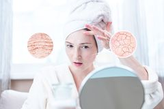 Young woman looking at dry skin with cracks and with wrinkles. Circles increase the skin like a magnifying magnifier stock image