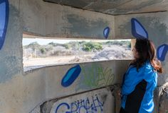 A young woman is looking through the embrasure in a concrete security separation fence on the border between Israel and Lebanon. royalty free stock photography