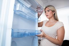 Young Woman Looking In Empty Fridge Royalty Free Stock Image