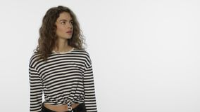 Young woman looking evaluating at copy space. Beautiful girl looking at product. Young woman looking evaluating at copy space on white background. Portrait of stock footage