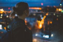 Young woman looking at evening city from skyscraper viewing plat Stock Images