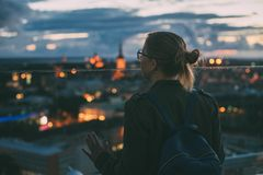Young woman looking at evening city from skyscraper viewing plat Royalty Free Stock Photography