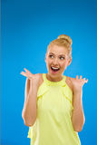 Young woman looking excited against blue background. Stock Image