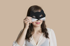Young woman looking through eye mask over colored background Royalty Free Stock Photo