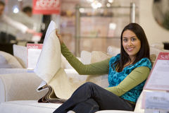 Young woman looking at fabic samples in shop, smiling, portrait Stock Photo