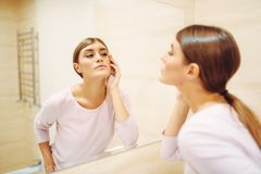 Woman looking on face at the mirror in bathroom. Young woman looking on face at the mirror in bathroom. Female person cares for skin. Morning facial cleaning stock photo