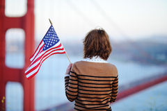 Young woman looking on famous Golden Gate bridge. Young woman with american flag looking on famous Golden Gate bridge in San Francisco, California, USA Royalty Free Stock Images