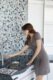 Young woman looking at faucet in model home kitchen Stock Image