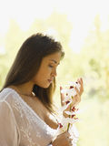 A young woman looking at a flower Royalty Free Stock Image