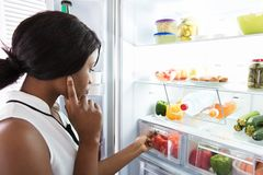 Young Woman Looking In Fridge. At Kitchen stock images