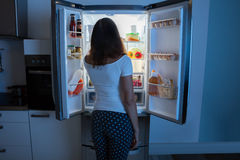 Young Woman Looking In Fridge. Rear View Of Young Woman Looking In Fridge At Kitchen royalty free stock photos