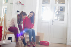Young woman looking at friend trying on footwear in store Stock Photo
