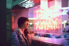 Young woman looking through the glass next to a club with a window with neon lights take away. Young woman looking through the glass next to a window with neon royalty free stock images
