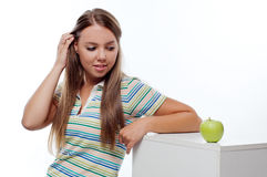 Young woman looking at green apple Royalty Free Stock Photos