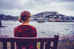 Young woman looking at harbor town. Rear view of a young woman sitting on a bench and admiring a harbor town Stock Photography