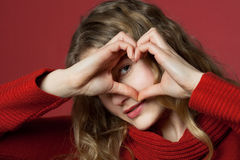 Young woman looking through heart. Young woman formed a heart with the hands Royalty Free Stock Image