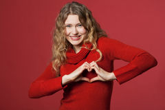Young woman looking through heart. Young woman formed a heart with the hands Stock Photos