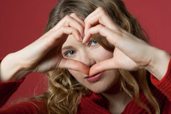Young woman looking through heart. Young woman formed a heart with the hands Royalty Free Stock Images