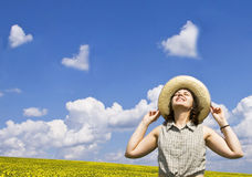Young woman looking at heart shaped clouds. Young happy woman looking at heart shaped clouds Royalty Free Stock Image