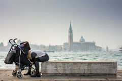 Young woman looking at her baby. Young woman looking at her baby in stroller Stock Images