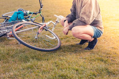 Young woman looking at her bicycle in park Stock Image