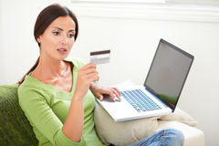 Young woman looking at her credit card Stock Images