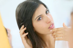 Young woman looking at her skin in the mirror Royalty Free Stock Image
