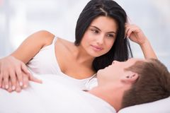 Young woman looking at her sleeping husband Stock Photos