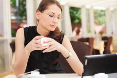 Young woman looking at her tablet computer and drinks c Stock Photos
