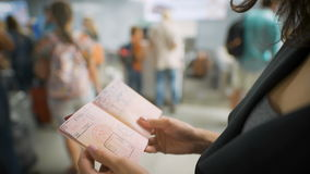 A young woman is looking at her visa in the passport stock video