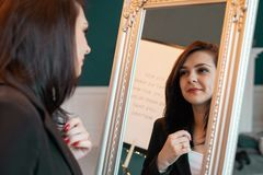 Young woman looking herself reflection in mirror at home stock images