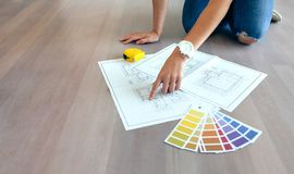 Young woman looking house plans. On the floor stock images