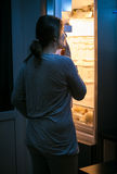 Young woman looking inside the fridge at late night Stock Photography