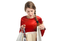 Young woman looking inside the shopping bags. Girl unhappy about the gift. Isolated on white Royalty Free Stock Image
