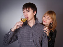 Young woman looking at its man which drinks win Royalty Free Stock Photography