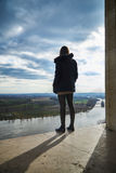 young woman is looking into the landscape on a terrace with dramatic clouds Royalty Free Stock Photo