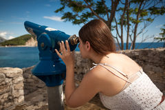 Young woman looking on landscape through touristic telescope Stock Image