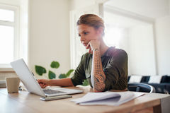 Young woman looking at laptop seriously. Royalty Free Stock Photography