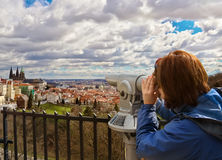 Young woman looking at Mala Strana and St. Vitus Cathedral in Pr. Young woman is looking through spyglass at Mala Strana (Little Quarter) and St. Vitus Cathedral Royalty Free Stock Photography