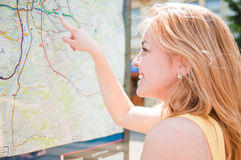 Young woman is looking on a map Royalty Free Stock Images