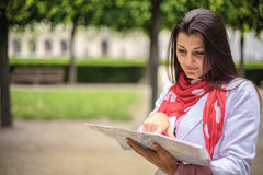 Young woman looking on the map at the city park Paris, France Royalty Free Stock Photo