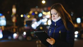 Young woman looking at a map on the tablet. Is on the background of the city at night stock video