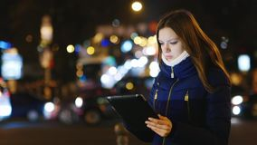 Young woman looking at a map on the tablet. Is on the background of the city at night stock footage