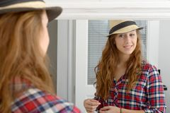Young woman looking in a mirror. A young woman looking in a mirror Royalty Free Stock Images