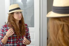 Young woman looking in a mirror. A young woman looking in a mirror Royalty Free Stock Photography
