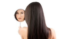 Young woman looking into a mirror. Royalty Free Stock Photo