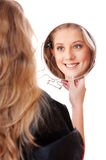 Young woman looking in the mirror Stock Photos